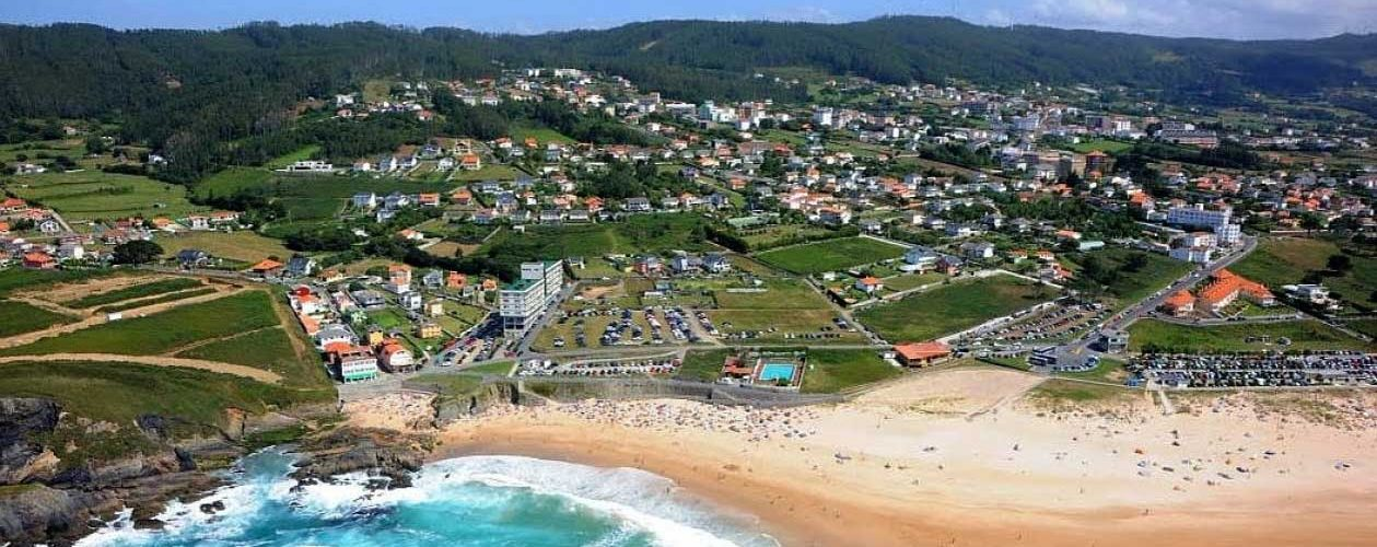 a birds-eye view of Valdoviño with the ocean and beach in the foreground and the village in the center