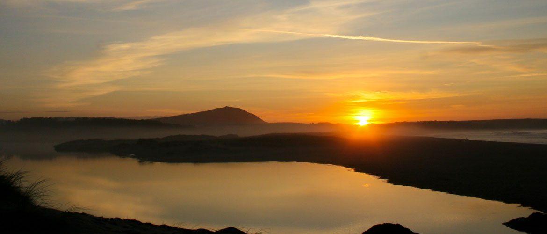 Sonnenuntergang mit Lagune von Frouxeira im Vordergrund und Meer im Hintergrund